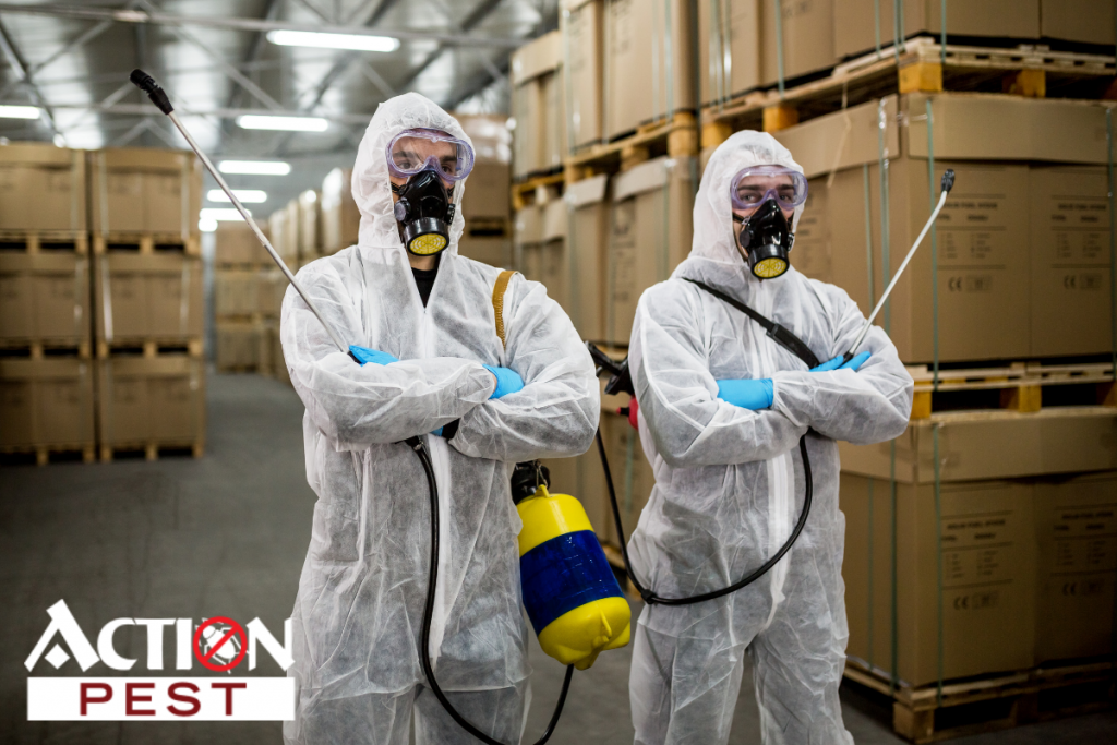 This image shows two people in pest control gear for commercial pest control inside of a warehouse.